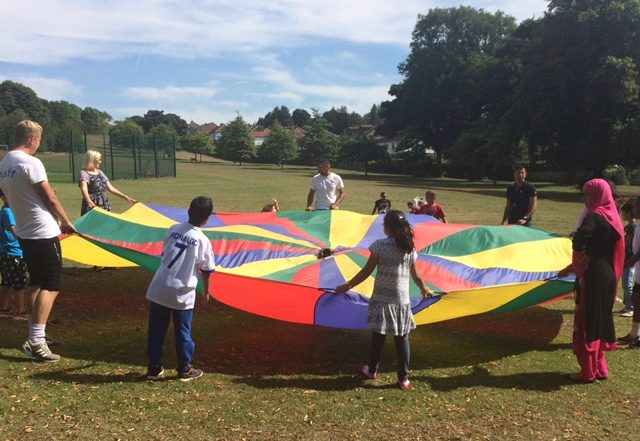 Photo of staff and volunteers playing with children using a giant parachute in the park