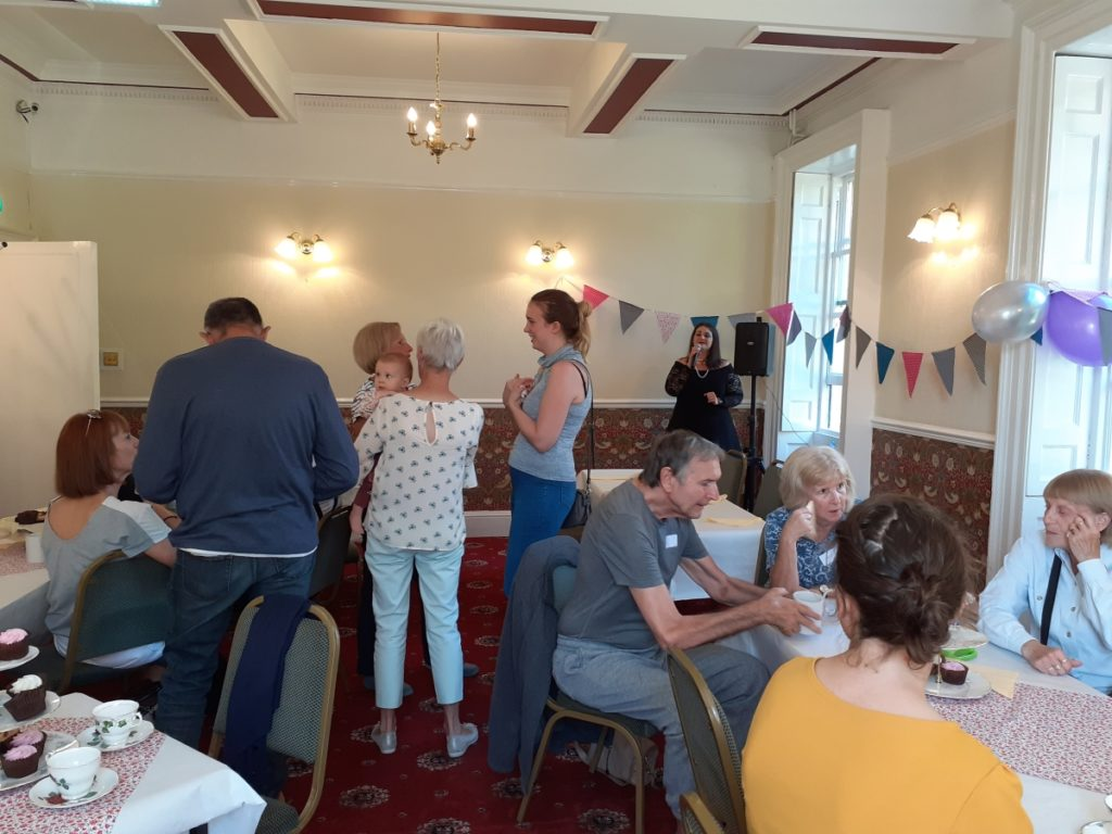 People chatting, with singer in background, at Dementia Cafe launch