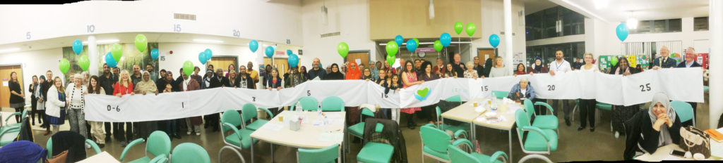 Photo of a lot of people holding up a long timeline at the DWB AGM, holding balloons