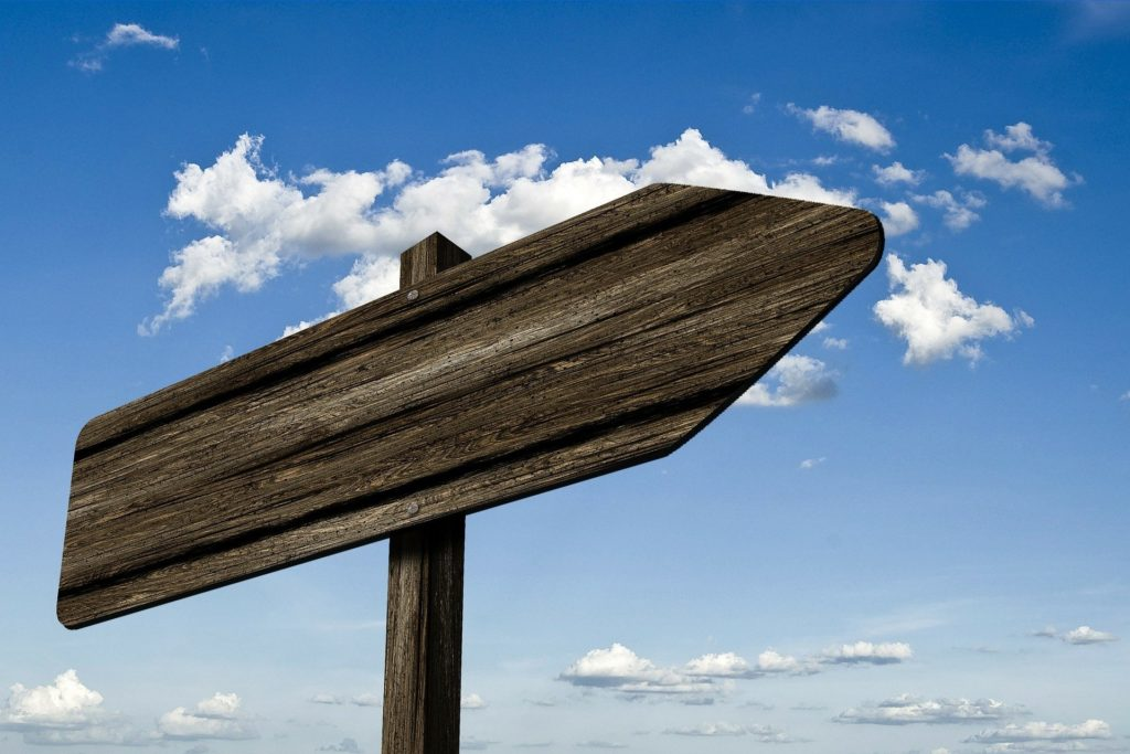 photo of a blank signpost against a blue sky