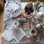 Photo of a table set for afternoon tea, with the contents of a VE Day themed activity pack