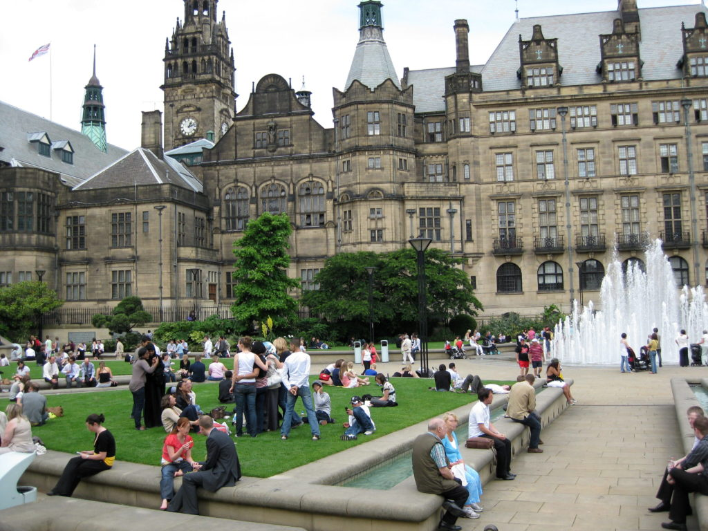 Photo of people sitting in Sheffield Peace Gardens with Town Hall behind