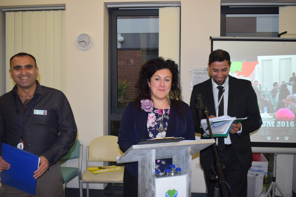 photo of Lucy Melleney, CEO of DWB, at a lectern with 2 smiling people behind her