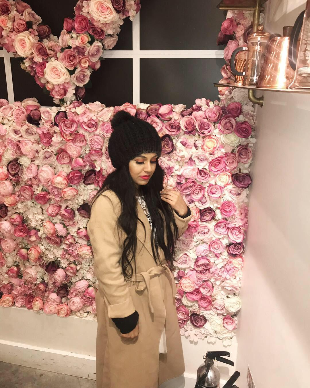 photo of Sayrish standing in front of a wall of pink flowers