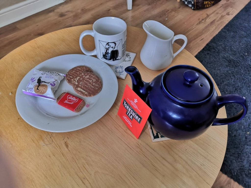 Photo of cup of tea, teapot and biscuits