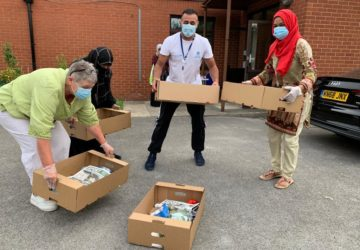photo of people wearing masks, carrying boxes of food