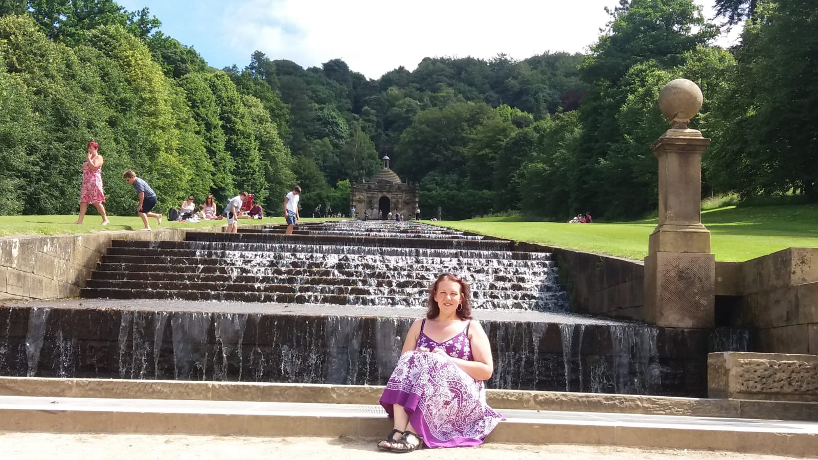 Photo of woman sitting by a fountain