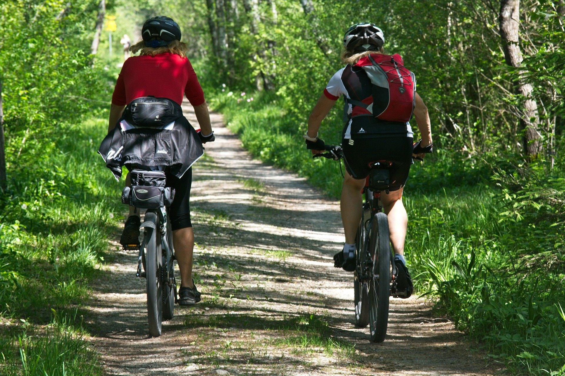 photo of 2 women riding bikes on a country lane