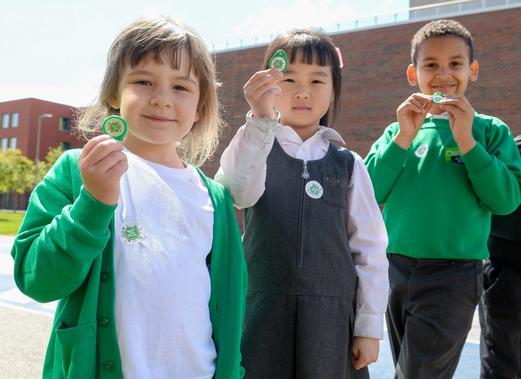 photo of children holding up tokens