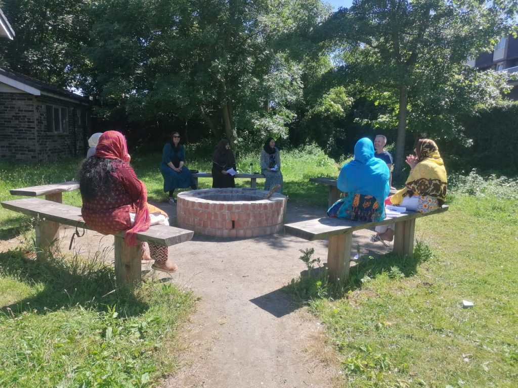 photo of women sitting in a circle on benches chatting