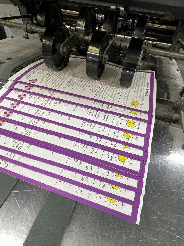copies of a newsletter on a printer