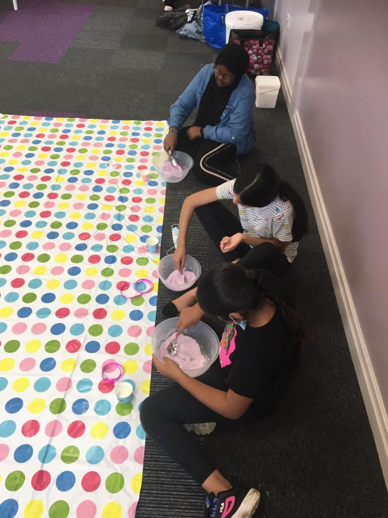 photo of children on the floor making slime in bowls
